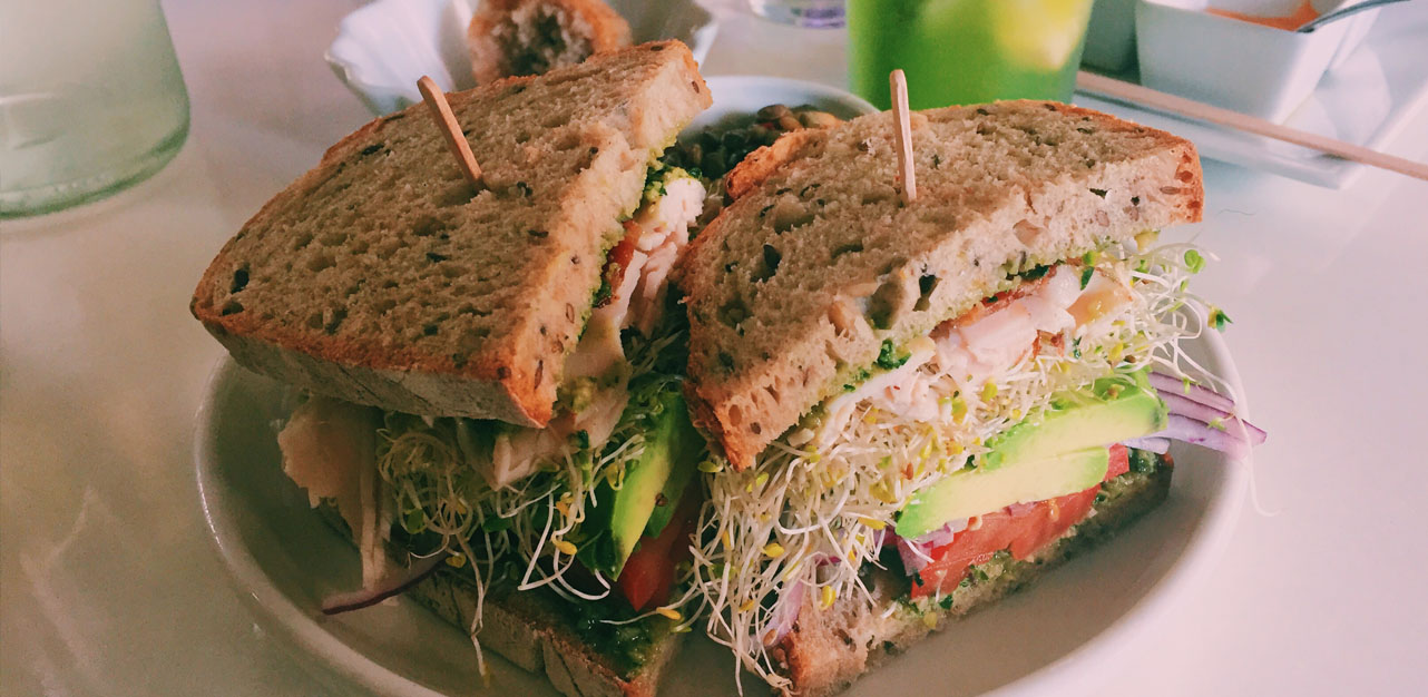 The Big Liho sandwich is filled with avocado, sprouts, homemade pesto, bacon, and more.